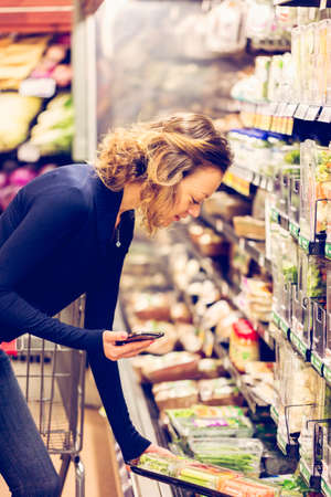 Young woman shopping in the fresh produce section at the grocery store. Stock Photo