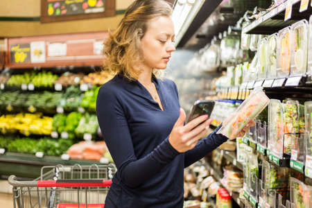 fresh produce: Young woman shopping in the fresh produce section at the grocery store. Stock Photo