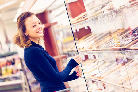 Young woman shopping in the bakery section at the grocery store.