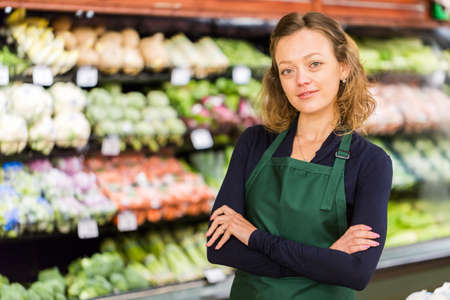 store clerk: Portrait of a grociery store clerk in front of a vegetable section of the store.