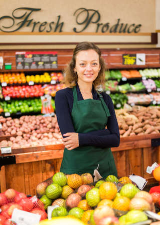 Portrait of a grociery store clerk in front of a vegetable section of the store.