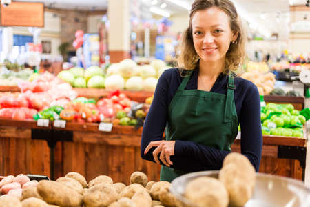 salesperson: Portrait of a grociery store clerk in front of a vegetable section of the store.