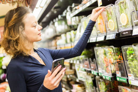 bring: Young woman shopping in the fresh produce section at the grocery store. Stock Photo