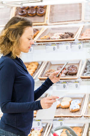 bakery store: Young woman shopping in the bakery section at the grocery store.