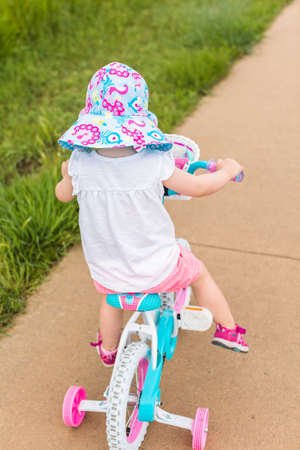 Toddler learning how to ride bicycle on the trail.