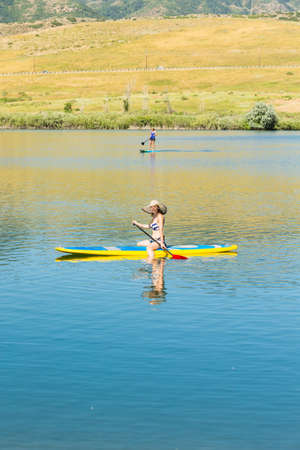 paddleboard: Young woman learning how to paddleboard on small pond. Stock Photo