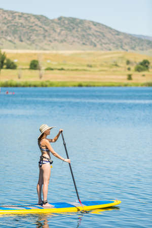 Young woman learning how to paddleboard on small pond. Stock Photo