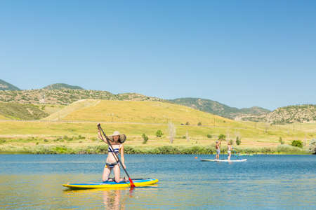 watersport: Young woman learning how to paddleboard on small pond. Stock Photo