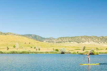 chatfield: Young woman learning how to paddleboard on small pond. Stock Photo