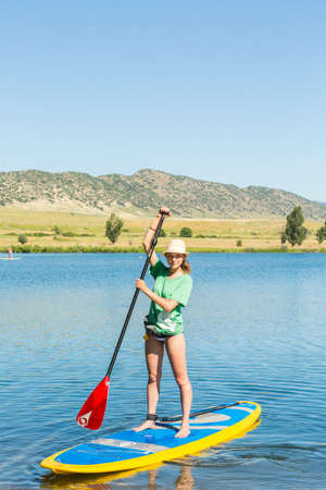 chatfield: Denver, Colorado, USA-July 13, 2016. Young woman learning how to paddleboard on small pond. Editorial