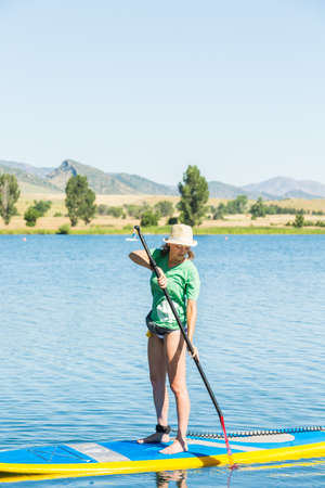 watersport: Denver, Colorado, USA-July 13, 2016. Young woman learning how to paddleboard on small pond. Editorial