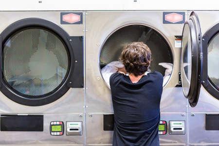 Adolescente que hace la colada en una lavandería pública. Foto de archivo - 60122930