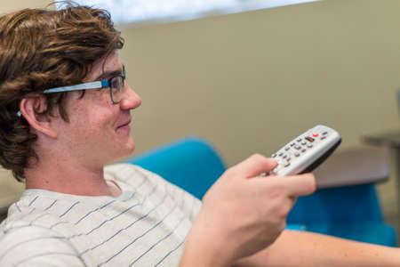 viendo television: Adolescente viendo la televisi�n en sala de prensa.