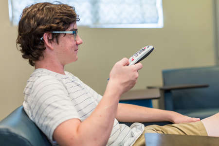 media room: Teenager watching television in media room. Stock Photo