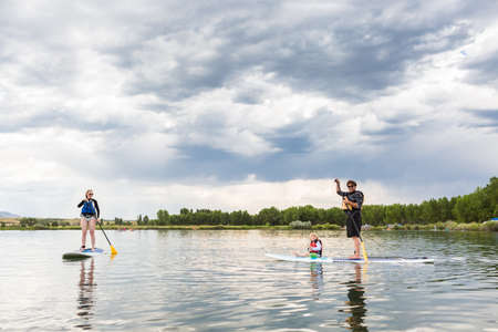 watersport: Denver, Colorado, USA-July 23, 2016. Family paddleboarding on small pond.