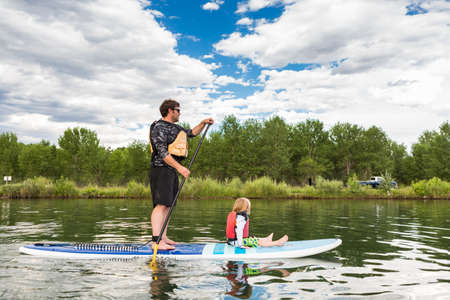 watersport: Denver, Colorado, USA-July 23, 2016. Recreational paddleboarding on small pond. Editorial