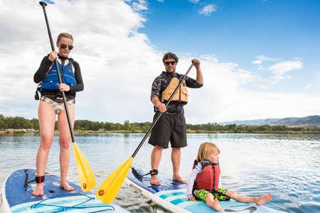 Denver, Colorado, USA-July 23, 2016. Family paddleboarding on small pond.