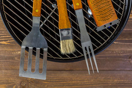 Stainless steel barbecue cooking set with wood handles.