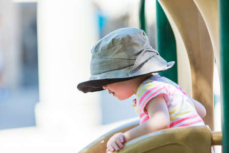 Toddler playing at outdoor playground.