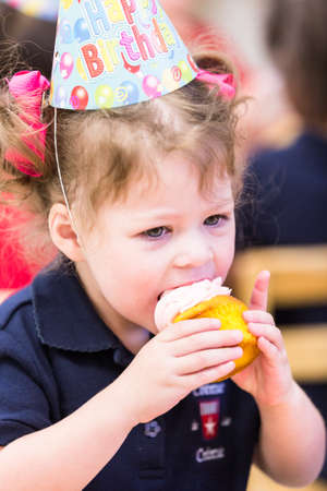 pastrie: Cute girl celebrating 3rd birthday with her friends at school.