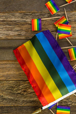 Rainbow Gay Pride small flags on wood background. Stock Photo
