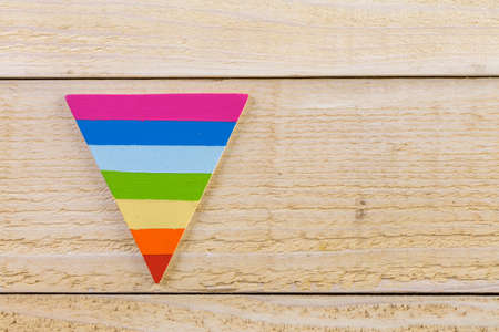 homosexuals: Rainbow Gay Pride triangle shape on a wood background.