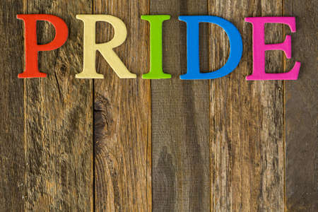 homosexuals: rainbow Gay Pride sign on a wood background. Stock Photo