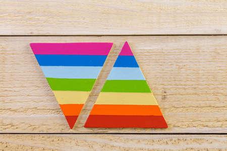 homosexuals: la forma del triángulo del arco iris del orgullo gay en un fondo de madera.
