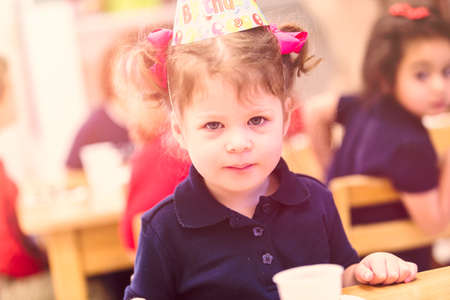 Cute girl celebrating 3rd birthday with her friends at school.