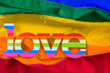Rainbow Gay Pride flag with Love sign. Stock Photo