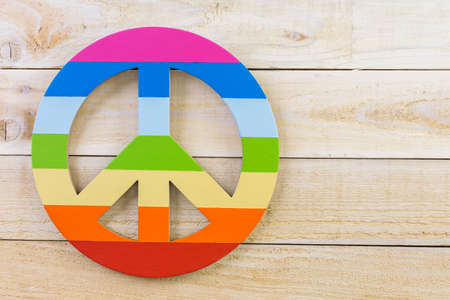 Rainbow Gay Pride Peace sign on wood background. Stock Photo