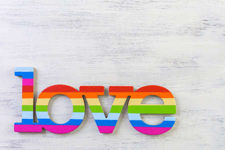Rainbow Gay Pride love sign on wood background.