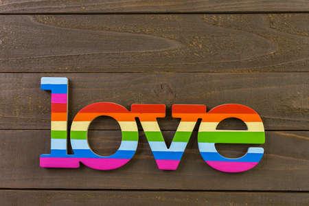 homosexuales: Arco iris del orgullo gay de la muestra del amor en el fondo de madera. Foto de archivo