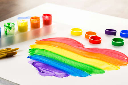 Painting Rainbow Gay Pride heart on a white paper.