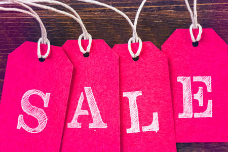 Tags with sale sign on wood board. Stock Photo