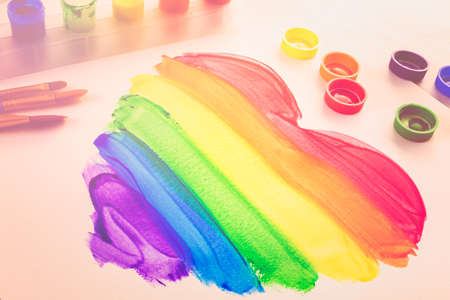transgender gay: Painting Rainbow Gay Pride heart on a white paper.