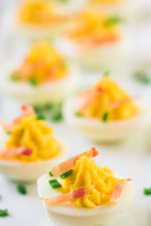 Deviled eggs garnished with green onions and bacon.
