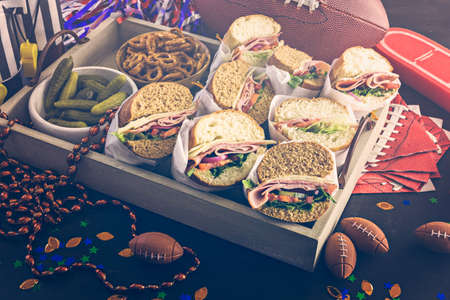 hoagie: Game day football party table with  sub sandwich and snacks. Stock Photo