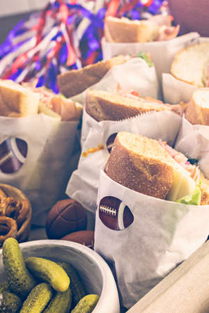hero sandwich: Game day football party table with  sub sandwich and snacks. Stock Photo
