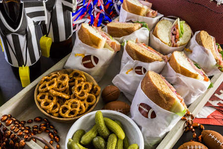Game day football party table with  sub sandwich and snacks. Stock Photo
