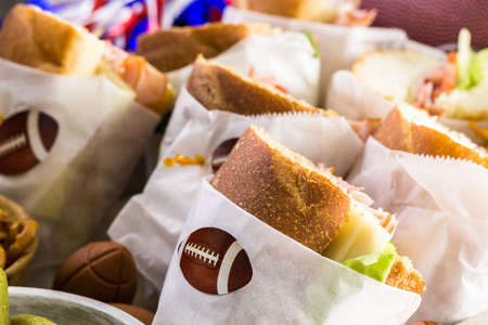 filled roll: Game day football party table with  sub sandwich and snacks. Stock Photo
