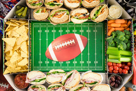 american hero: Step by step. Filling in football snack stadium with sub sandwiches, veggies and chips.