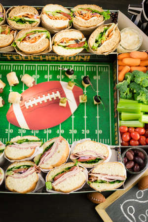 hoagie: Football Snack Stadium filled with sub sandwiches, veggies and chips.