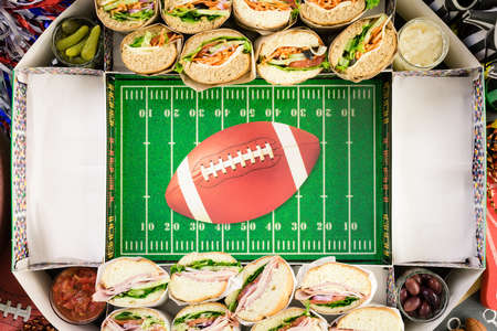 Step by step. Filling in football snack stadium with sub sandwiches, veggies and chips.