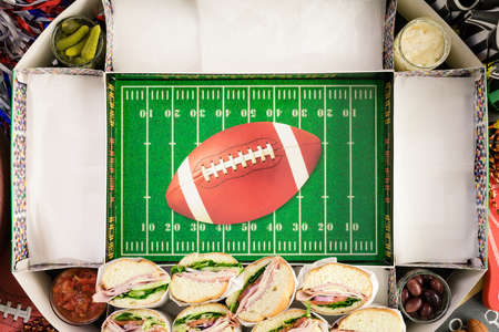 hoagie: Step by step. Filling in football snack stadium with sub sandwiches, veggies and chips.