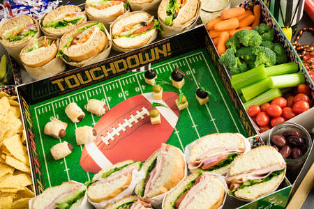 hero sandwich: Football Snack Stadium filled with sub sandwiches, veggies and chips.