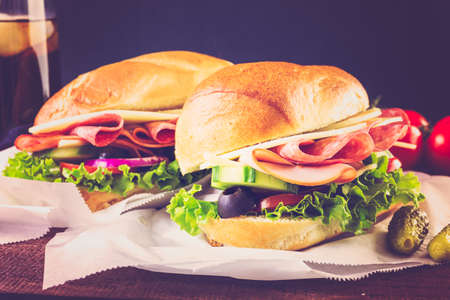 hero sandwich: Sub sandwich with fresh vegetables, lunch meat and cheese on hoagie roll.