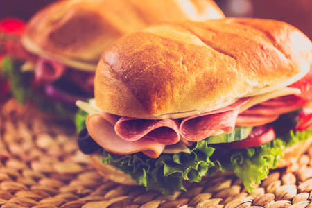 filled roll: Sub sandwich with fresh vegetables, lunch meat and cheese on hoagie roll.