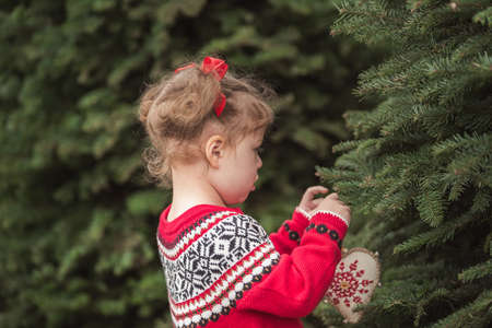 Little girl in red dress on the Christmas tree farm. Stock Photo