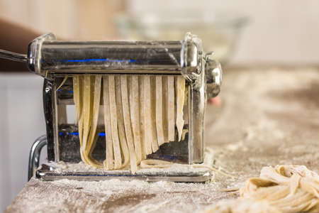Preparing home made pasta with pasta maker.